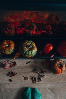Widok z góry na kominek ozdobiony dyniami i suchymi jesiennymi liśćmi oraz pomarańczową świecą. przytulny dom koncepcja. przygotowanie do halloween.