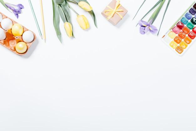 Widok z góry na kompozycję wielkanocną: kwiaty, kolorowe jajka i farby akwarelowe