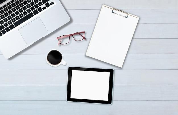 Widok z góry na komputer typu tablet notebook z drewnianą podłogą w stylu biurowym.