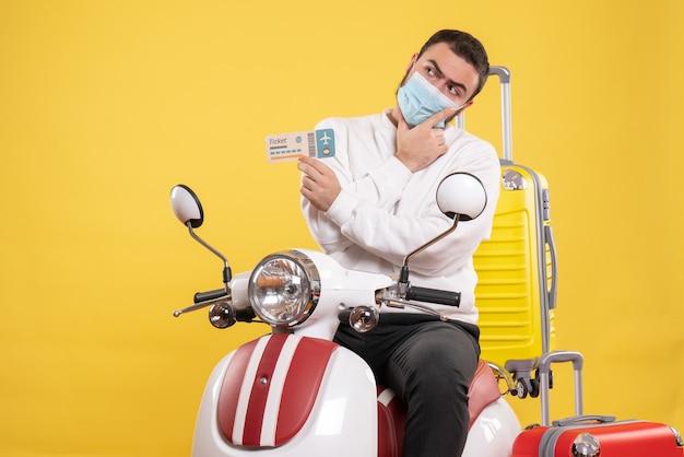 Widok z góry na koncepcję podróży z myślącym facetem w masce medycznej siedzącej na motocyklu z żółtą walizką na nim i trzymającym bilet