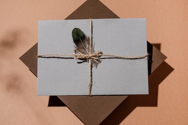 Widok z góry na kopertę ze sznurkiem i piórkiem