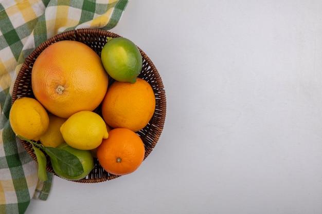 Widok z góry na kopię grejpfruta z pomarańczami i cytrynami w koszu z żółtym zielonym ręcznikiem w kratkę na białym tle