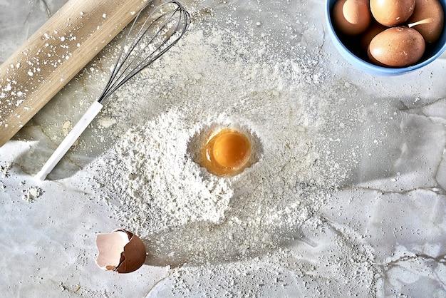 Widok z góry na kopiec podłogi z jajkiem, trzepaczką i drewnianym wałkiem do ciasta