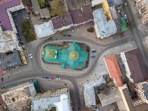 Widok z góry na kopułę kościoła św. mikołaja pristika, dachy domów i drogę z zaparkowanymi samochodami, dzielnica podol. kijów, ukraina. zdjęcie drona