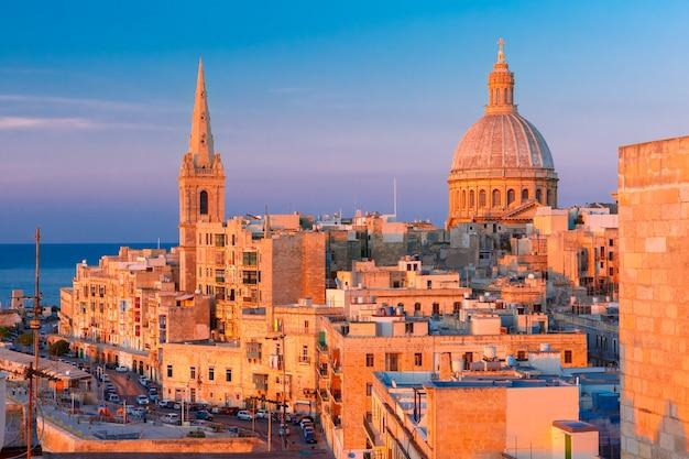 Widok z góry na kopuły kościołów i dachy o pięknym zachodzie słońca z kościołem matki bożej z góry karmel i anglikańską prokatedrą św. pawła, valletta, stolica malty