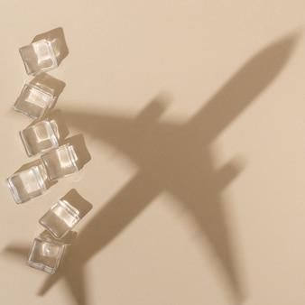 Widok z góry na kostki lodu z cieniem samolotu na kolor piasku
