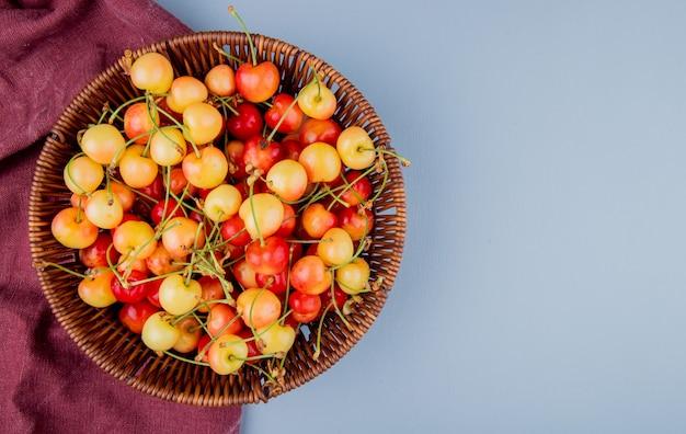 Widok z góry na kosz pełen żółtych i czerwonych wiśni na szmatce bordo po lewej stronie i niebieskim z miejscem na kopię