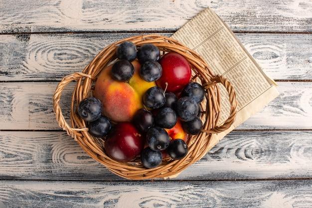 Widok z góry na kosz z tarniną, brzoskwiniami i śliwkami na szarym biurku