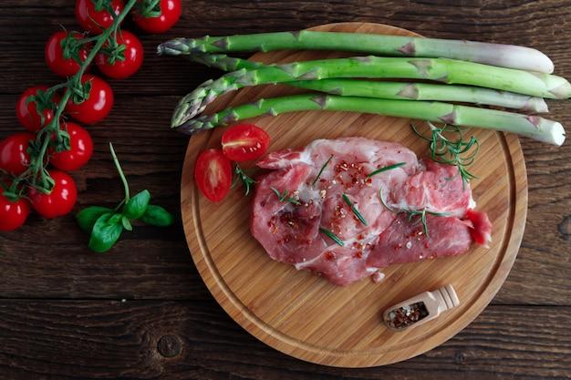 Widok z góry na kotlety wieprzowe w przyprawach na drewnianym stole ze świeżymi zielonymi szparagami i pomidorami cherry.