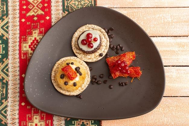 Widok z góry na krakersy i ciasta wewnątrz brązowego talerza z ziarnami kawy