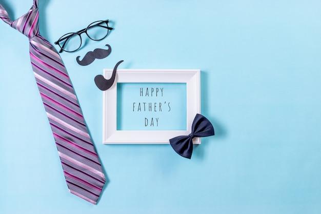 Widok z góry na krawat, okulary, wąsy z tekstem dzień szczęśliwego ojca na niebieskim pastelowym tle