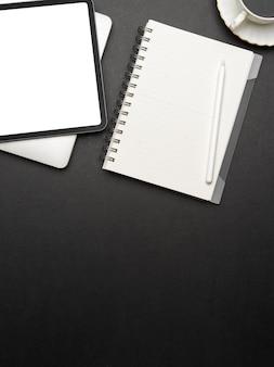 Widok z góry na kreatywny płaski obszar roboczy z cyfrowym tabletem, notatnikiem, filiżanką kawy i miejscem na kopię, ścieżką przycinającą