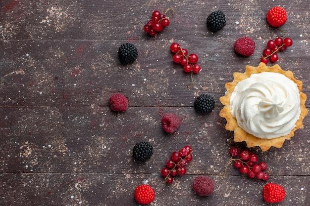 Widok z góry na kremowe pyszne ciasto wraz z różnymi jagodami rozłożonymi na brązowej podłodze ciastko z kremem jagodowym do pieczenia