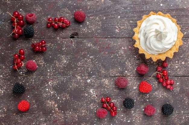 Widok z góry na kremowe, pyszne ciasto wraz z różnymi jagodami rozłożonymi na brązowym, owocowym ciastku do pieczenia