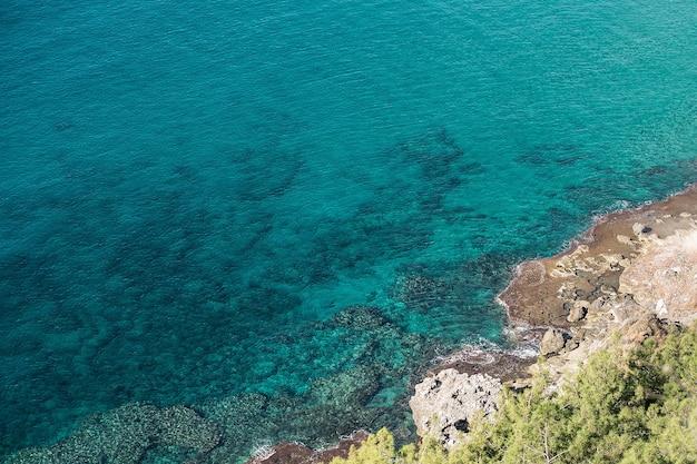 Widok z góry na krystalicznie czyste turkusowe morze.