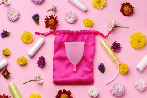 Widok z góry na kubek menstruacyjny otoczony kwiatami