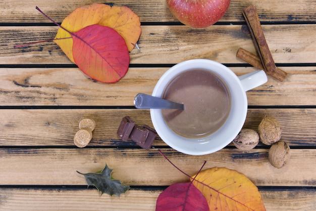 Widok z góry na kubek pełen napoju czekoladowego wśród czerwonych liści na drewniane tła