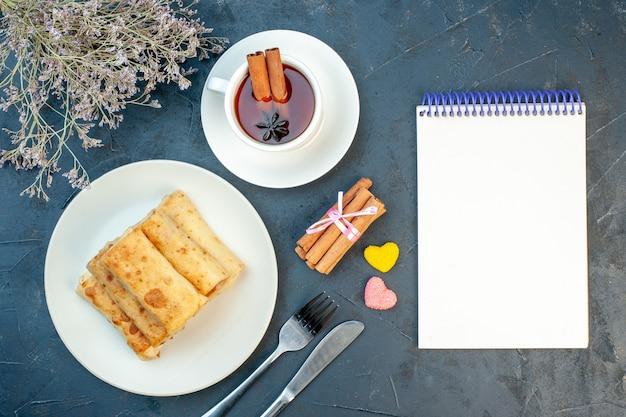 Widok z góry na lavash wraps na talerzu i sztućce zestaw filiżankę czarnej herbaty cynamonowe limonki na czarnym tle