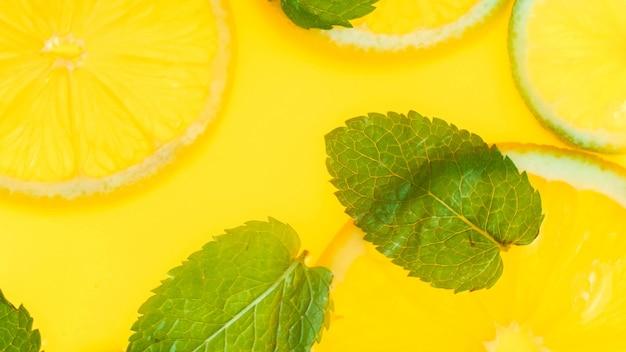 Widok z góry na liście mięty i plastry pomarańczy w lemoniadzie lub świeżym soku pomarańczowym.
