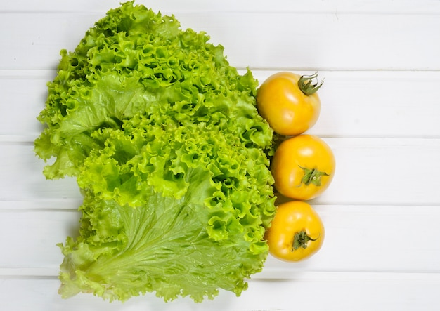 Widok z góry na liście zielonej sałaty z dojrzałymi pomidorami