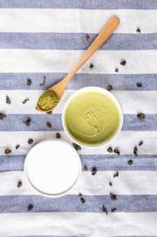 Widok z góry na lody matcha z zielonej herbaty w białym papierowym kubku z proszkiem matcha