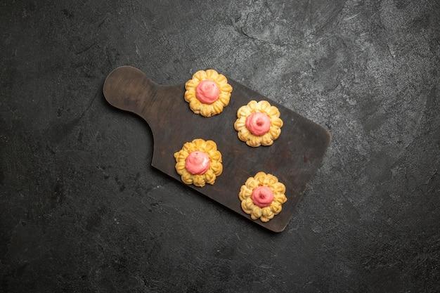 Widok z góry na małe ciasteczka cukrowe z kremem truskawkowym na szarej powierzchni