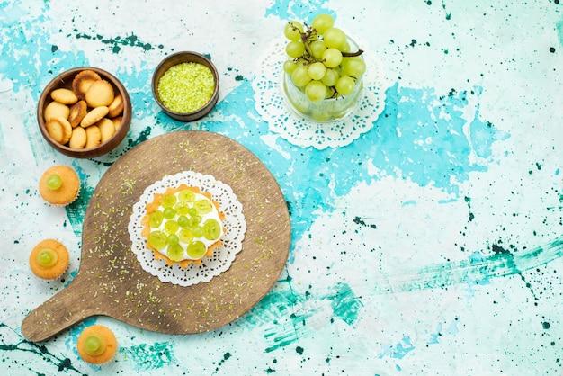 Widok z góry na małe ciasto z pyszną śmietaną i plasterkami i świeżymi ciasteczkami z zielonych winogron na białym tle na niebieski, słodki cukier owocowy ciasto