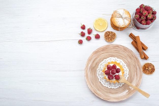 Widok z góry na małe ciasto ze śmietaną i malinami oraz cynamonowe ciasteczka kanapkowe na lekkiej podłodze ciasto owocowe ciasto jagodowe herbatniki słodkie