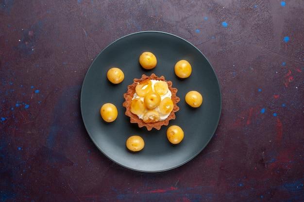 Widok z góry na małe kremowe ciasto ze świeżymi czereśniami wewnątrz talerza na ciemnej powierzchni