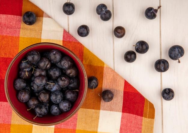Widok z góry na małe kwaśne niebiesko czarne owoce tarniny na czerwonej misce z tarniny na białym tle na białym tle drewniane