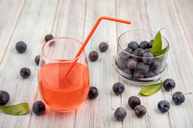 Widok z góry na małe kwaśne niebiesko-czarne tarniny na szklanej misce z sokiem na szklance z tarniny odizolowane na szarym drewnianym tle