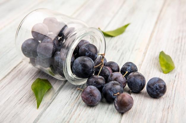 Widok z góry na małe kwaśne niebiesko-czarne tarniny wypadające ze szklanego słoika na szarym tle drewnianych