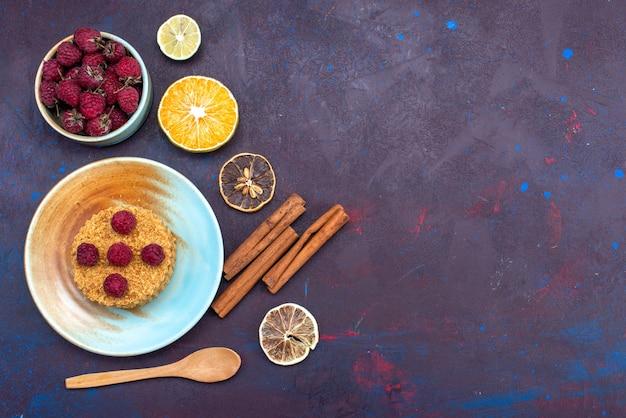 Widok z góry na małe okrągłe ciasto ze świeżymi malinami wewnątrz talerza z owocami na ciemnoniebieskiej powierzchni