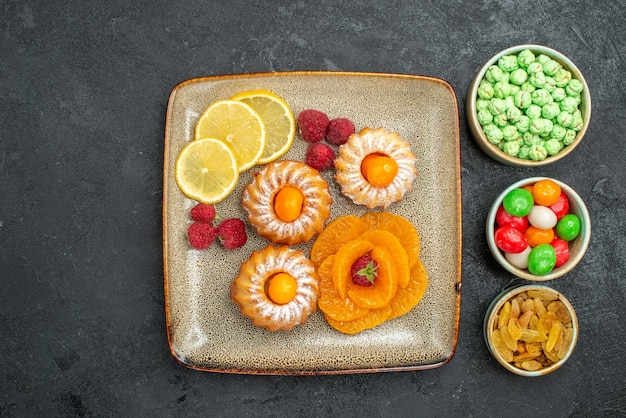 Widok z góry na małe pyszne ciasta z plasterkami cytryny, mandarynki i cukierki na ciemnym