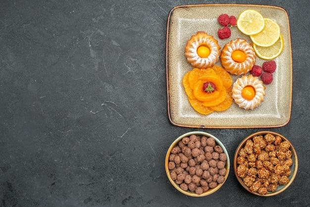 Widok z góry na małe pyszne ciasta z plasterkami cytryny, mandarynki i cukierki na szaro