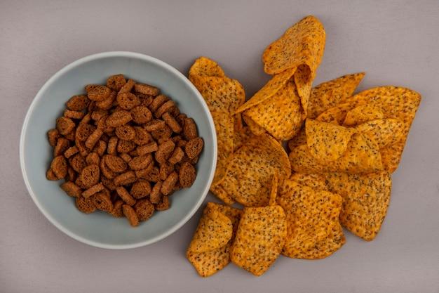 Widok z góry na małe suchary żytnie na miskę z smacznymi chipsami ziemniaczanymi na białym tle