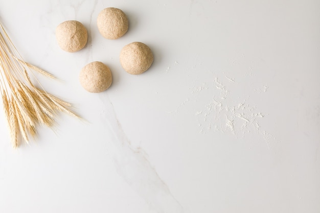 Widok z góry na marmurowy stół z czterema formowanymi ciastami chlebowymi, pszenicą i mąką z miejscem na tekst