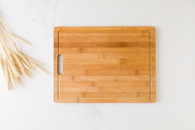 Widok z góry na marmurowy stół z drewnianą deską pośrodku, pszenicą i miejscem na tekst