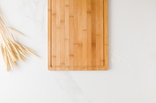 Widok z góry na marmurowy stół z drewnianą deską, pszenicą i mąką z miejscem na tekst