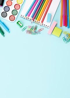 Widok z góry na materiały szkolne z powrotem z akwarelą i kopiować miejsca