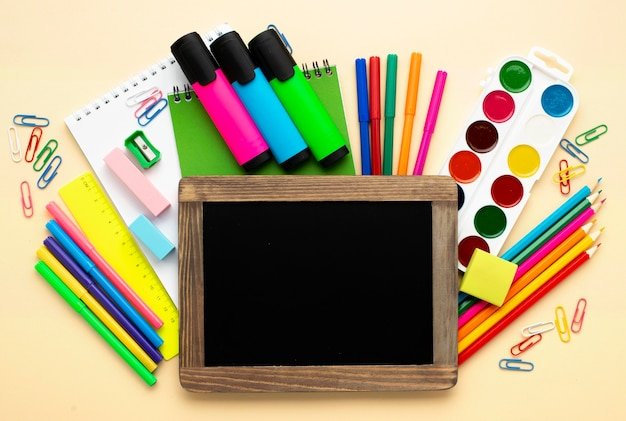 Widok z góry na materiały szkolne z powrotem z kolorowymi kredkami i akwarelą