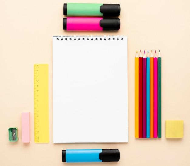 Widok z góry na materiały szkolne z powrotem z notatnikiem i kredkami