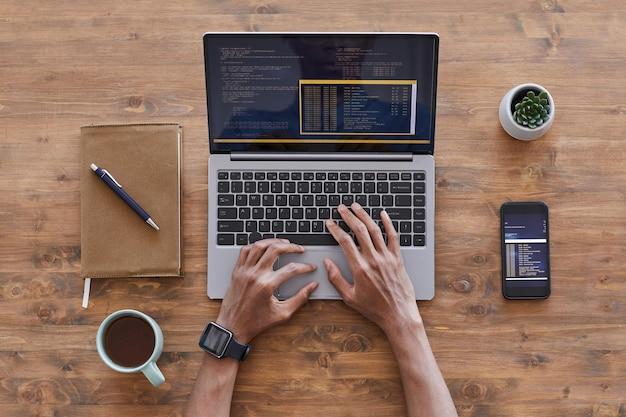 Widok z góry na męskie dłonie pisząc na klawiaturze laptopa podczas pisania kodu na drewnianym biurku z teksturą w studio rozwoju it, miejsce na kopię