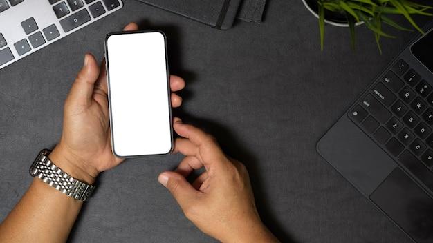Widok z góry na męskie ręce trzymające lub używające smartfona na biurku smartfon na czarnym tle