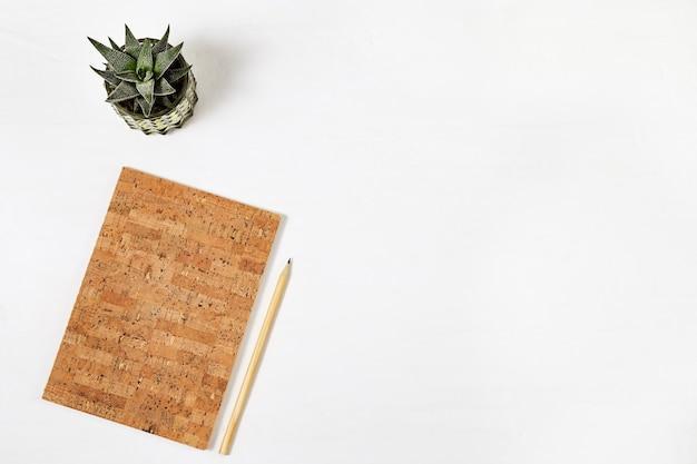Widok z góry na miejsce do pracy, notatnik z okładką z naturalnego korka, drewniany ołówek i roślina domowa