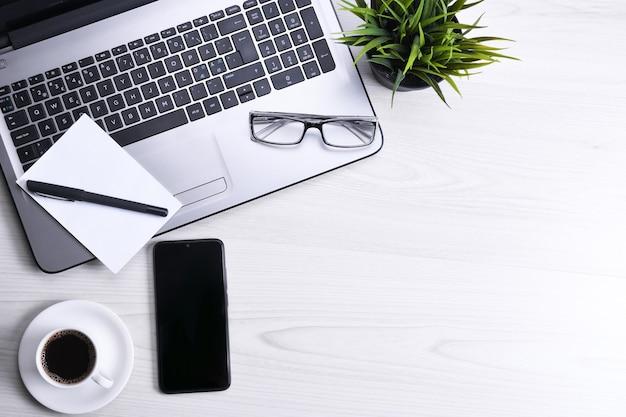 Widok z góry na miejsce do pracy w biurze, drewniany stół na biurko z laptopem, klawiaturą, długopisem, okularami, telefonem, notatnikiem i filiżanką kawy.