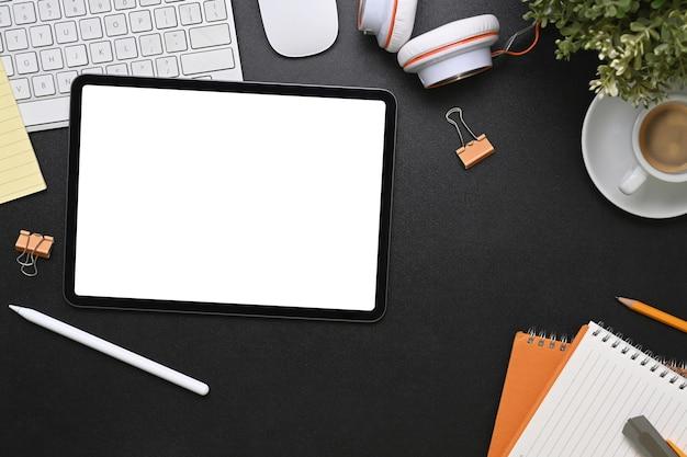Widok z góry na miejsce pracy projektanta graficznego z tabletem, filiżanką kawy, notatnikiem, słuchawkami i klawiaturą na czarnej skórze.