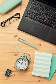 Widok z góry na miejsce pracy z laptopem i artykułami biurowymi