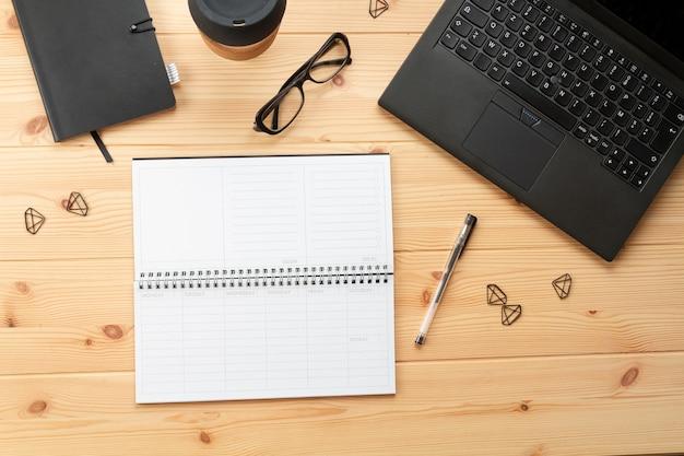 Widok z góry na miejsce pracy z laptopem i materiałami biurowymi