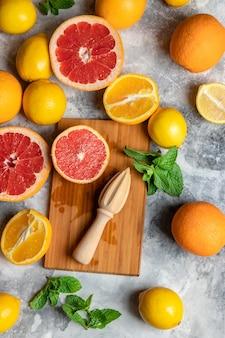 Widok z góry na mieszankę kompozycji świeżych owoców cytrusowych z pomarańczami, cytrynami, grejpfrutem, miętą i drewnianą deską do krojenia i wyciskarką lub prasą ręczną, wielobarwny streszczenie tło dla miejsca kopiowania